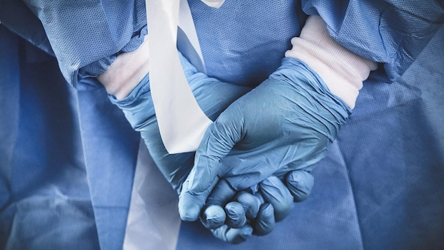 Une infirmière qui porte des gants de caoutchouc joint ses mains derrière son dos.