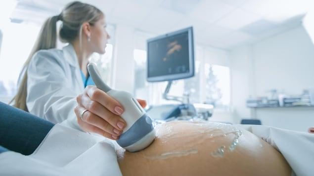 Gros plan sur le ventre d'une femme enceinte, pendant qu'une radiologue réalise une échographie.