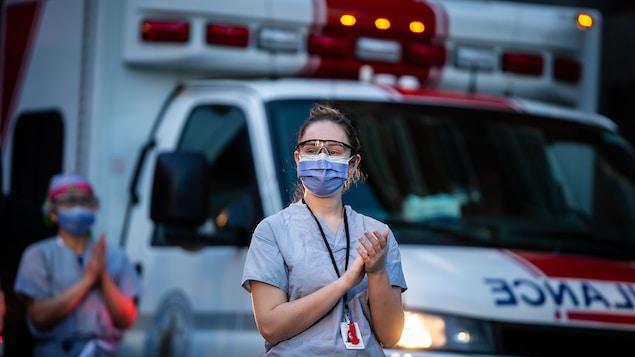 Deux femmes portant un masque devant une ambulance.