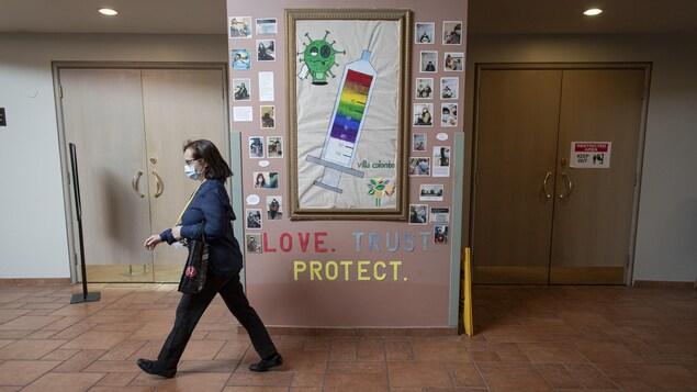 Une infirmière passe devant un panneau qui fait la promotion de la vaccination au foyer des soins Villa Columbo de Toronto.