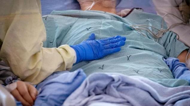 Une infirmière s'occupe d'un patient suspecté d'avoir le COVID-19 dans une unité de soins intensifs de Toronto.