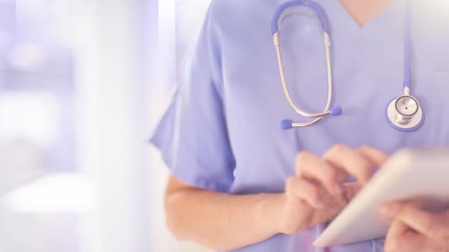 Une infirmière praticienne utilise une tablette électronique.