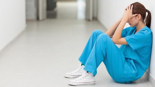 Une infirmière assise sur le sol se tient la tête