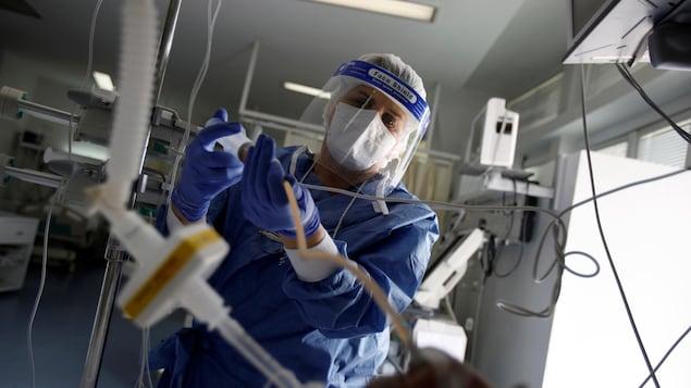 Une infirmière raccorde des tubes dans une unité de soins intensifs.