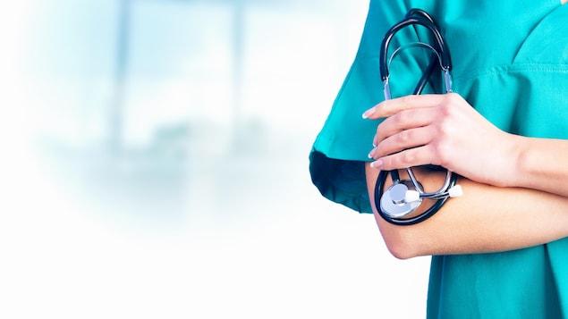 Une main d'infirmière tenant un stéthoscope.