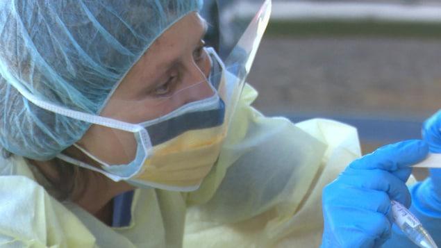 Une infirmière portant une visière et un masque effectue un test de dépistage de la COVID-19.