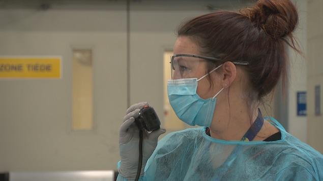 Une infirmière qui porte un masque parle dans un radio-émetteur lors de la pandémie de COVID-19 au Québec, le 9 avril 2020