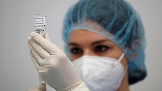 Une infirmière prépare une dose de vaccin.
