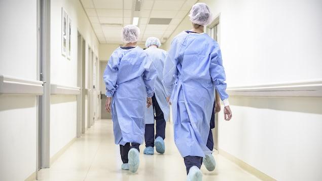 Des infirmières marchent de dos dans le corridor d'un hôpital.