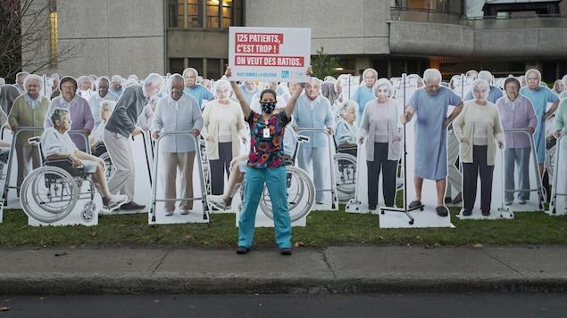 Une membre de la FIQ tient une pancarte à bout de bras et est entourée de dizaines d'effigies représentant des patients de CHSLD.