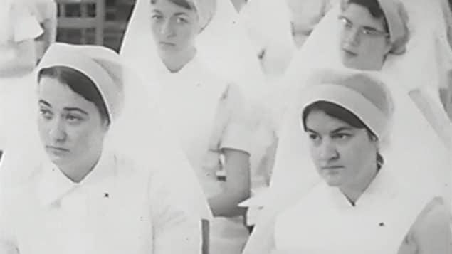 De jeunes femmes qui portent l'uniforme (robe et coiffe) sont assises dans une classe.