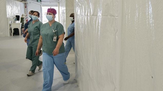 Quatre infirmières masqués marchent dans un corridor.