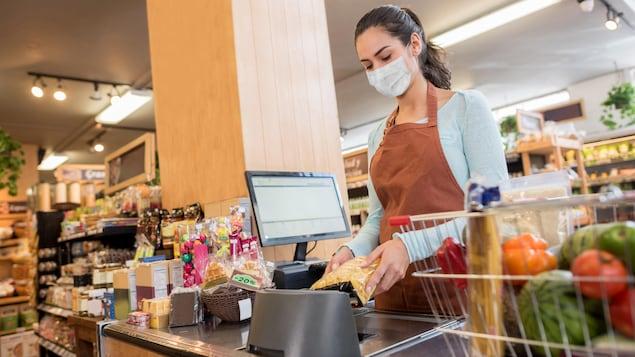 عاملة أمام صندوق تضع كمامة  في متجر.