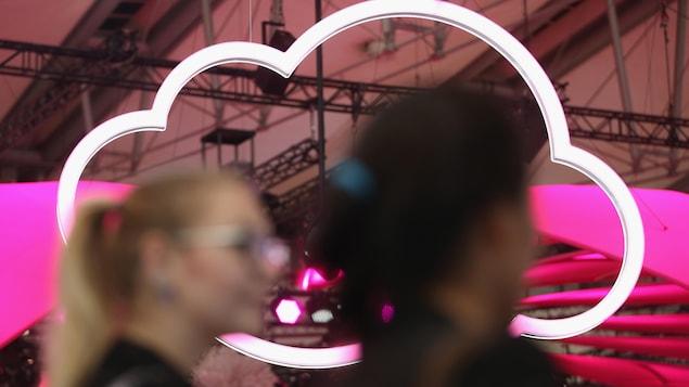 Deux femmes passent devant le logo d'un nuage suspendu au plafond d'une exposition technologique en Allemagne.