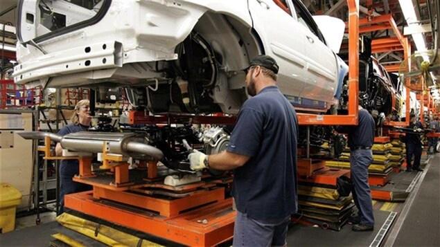 Des travailleurs de GM installent un pot d'achoppement à l'usine.