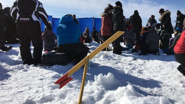Plusieurs parents et leurs enfants patientaient à côté de leur brimbale de pêche,