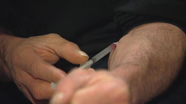 Un homme s'injecte de l'héroïne.