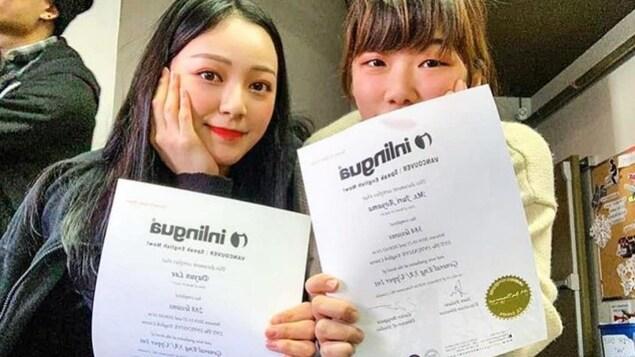 Deux étudiants montrent leurs diplômes.
