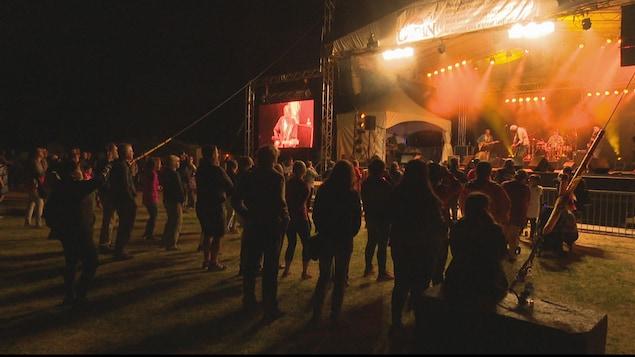 Un public debout assiste à un spectacle.