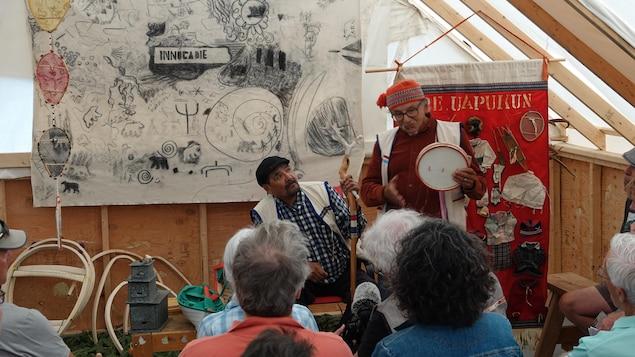 Deux hommes en tenue traditionnelle en prestation devant un public au festival Innucadie.