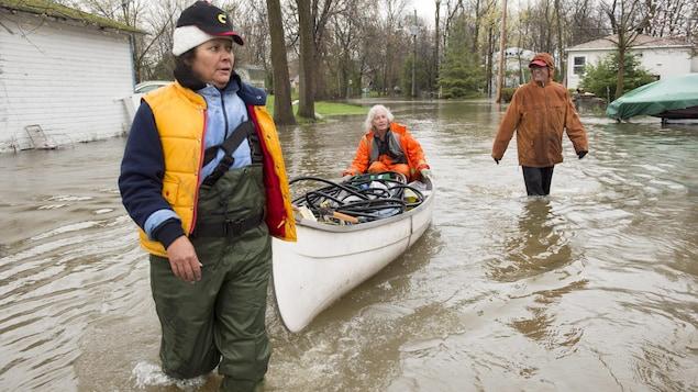 Des citoyens de L'Île-Bizard-Sainte-Geneviève transportent des biens à bord d'un canot dans les rues inondées de la municipalité.