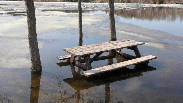 Une table de pique-nique entourée d'eau.