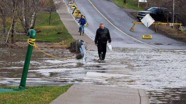 Un homme traverse une rivière qui passe par-dessus une route.