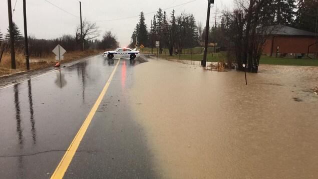 Une rue inondée et une voiture de police au loin bloquant accès à la route.