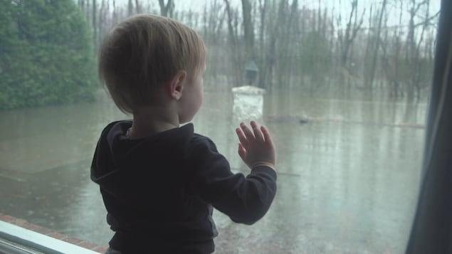 Un enfant appuyé à une fenêtre.