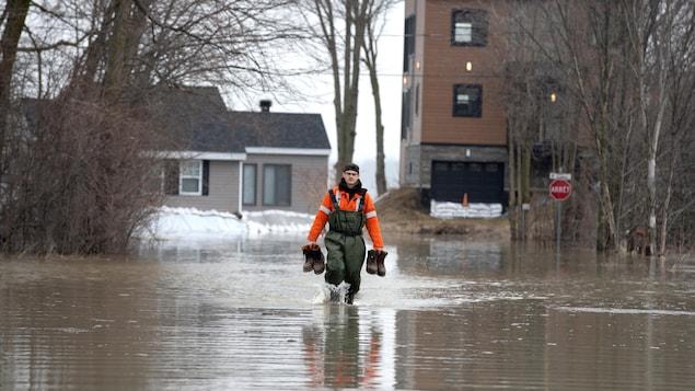 Un homme marche dans l'eau avec des bottes dans ses mains.