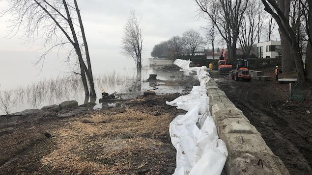 Des blocs de béton sont disposés en digue devant la rivière.
