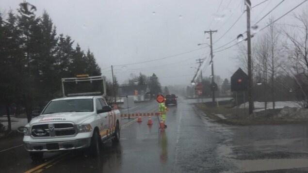 Une voiture et une barrière bloquent la route.