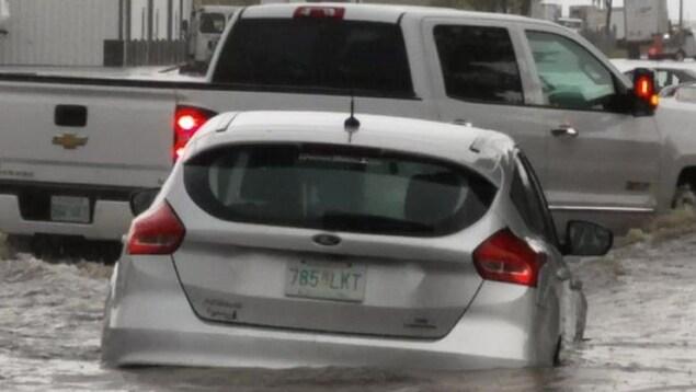Des voitures roulent dans une rue inondée de Swift Current.