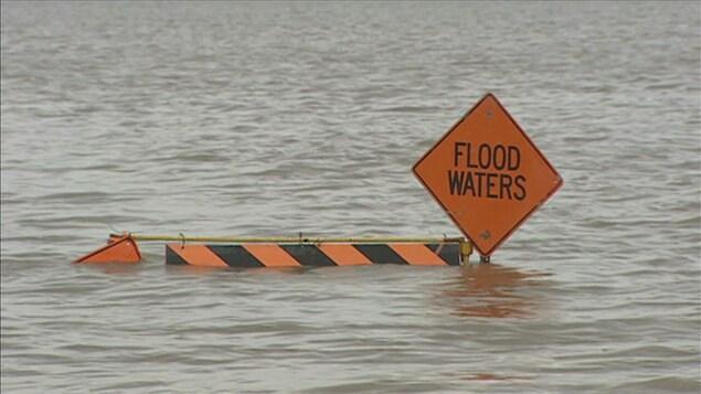 """Un panneau qui indique """"Flood Waters"""", planté dans l'eau."""