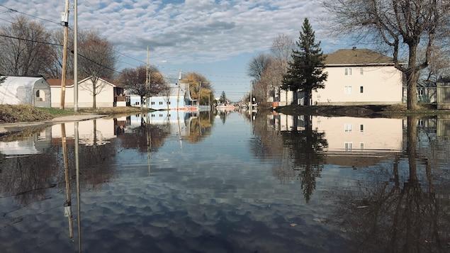 Les nuages se reflètent dans la rue entièrement inondée.