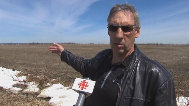 Un homme portant des verres fumés répond aux questions de la journaliste.
