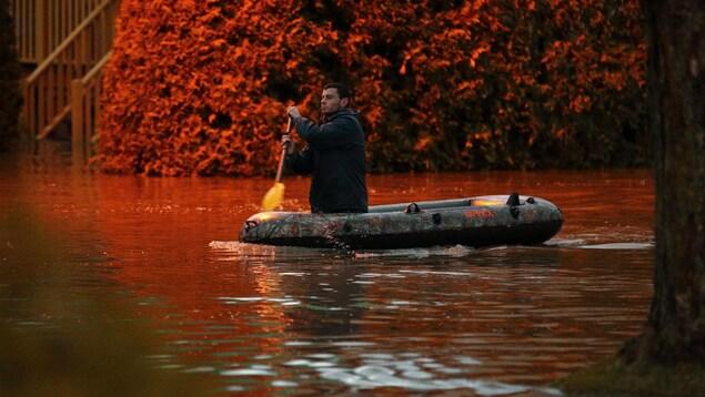 Un résident de Sainte-Marie se déplace avec un canot de fortune dans la ville inondée.