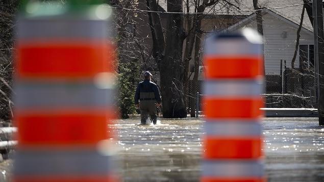 Un homme en pantalons et bottes de pluie marche dans la rue inondée. Au premier plan, des cônes de circulation.