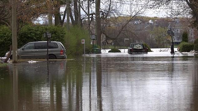 Une voiture stationnée dans une entrée de garage et un autre véhicule stationné au bout d'une rue sont entourées d'eau