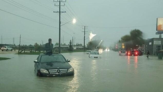 Un homme est assis sur le toit de sa voiture au milieu d'une rue innondée.