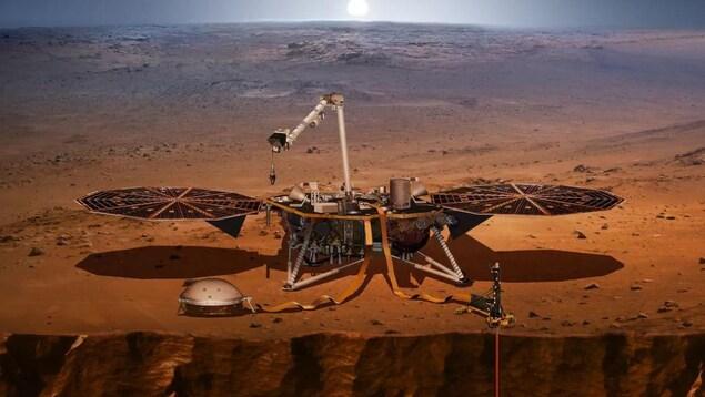 Un engin équipé de deux panneaux solaires est posé sur une terre sèche et orangée déserte.