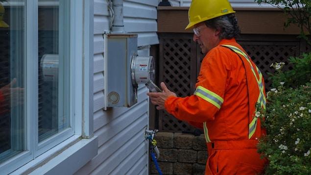 Étienne Lagueux, inspecteur à la protection des revenus d'Hydro-Québec, effectue des vérifications sur un compteur.