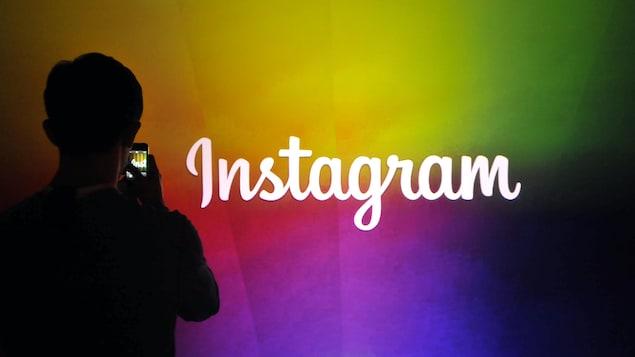 Un homme prend en photo le logo d'Instagram écrit en blanc sur un mur multicolore.