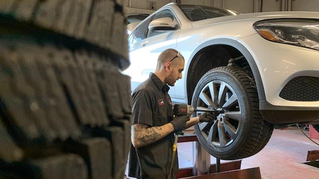 Un garagiste procède à un changement de pneu.