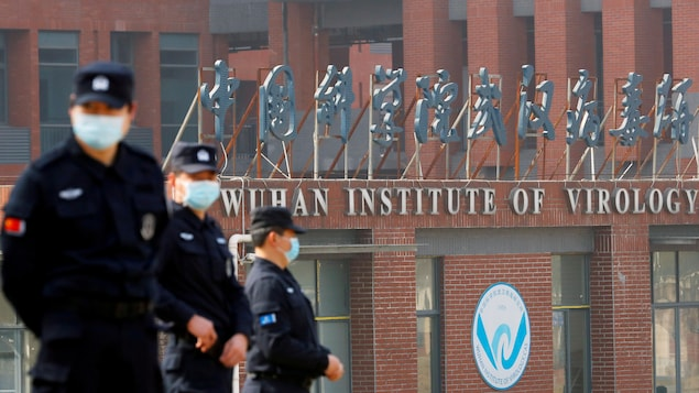Security guards wearing masks are standing in front of Wuhan Institute of Virology.