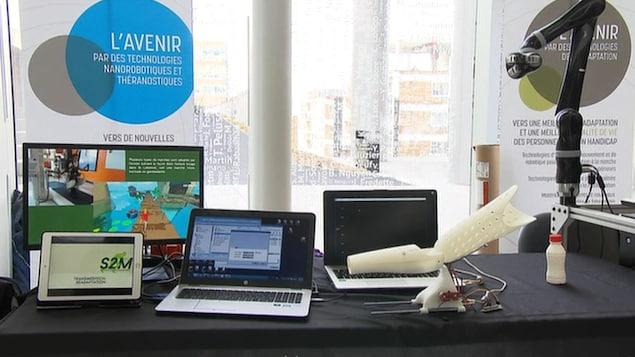 Des ordinateurs, une prothèse et un bras robotisé dans le cadre d'une présentation de l'Institut TransMedTech au CHU Sainte-Justine, à Montréal
