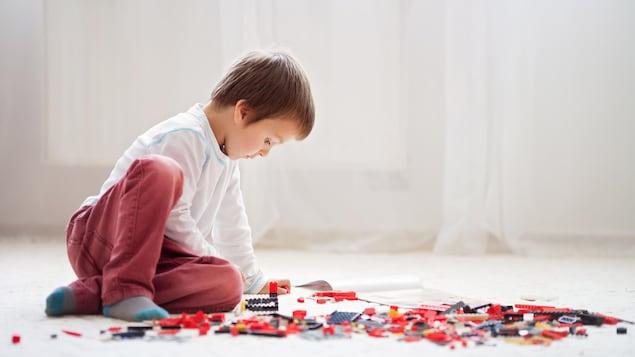 Un enfant est assis par terre. Autour de lui, des blocs de constructions rouges, noirs et gris sont  près de lui.
