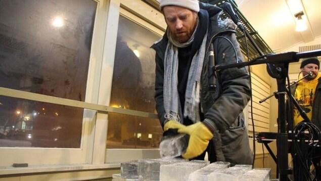 Un homme debout qui tient un morceau de glace. Près de lui des micros et d'autres instruments.