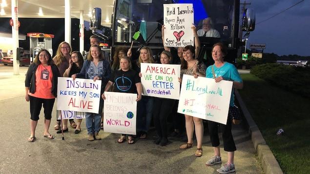 Des personnes portent des pancartes réclamant davantage d'accès à l'insuline devant un autocar.