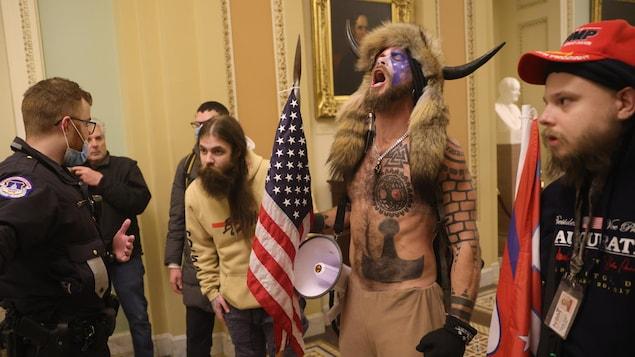 Un homme barbu et un homme vêtu d'un costume Viking parlent à un policier.